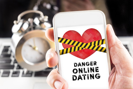 Foto de Hand holding mobile with caution tape on heart and Danger online dating  on screen with clock and laptop at background, Internet love concept. - Imagen libre de derechos