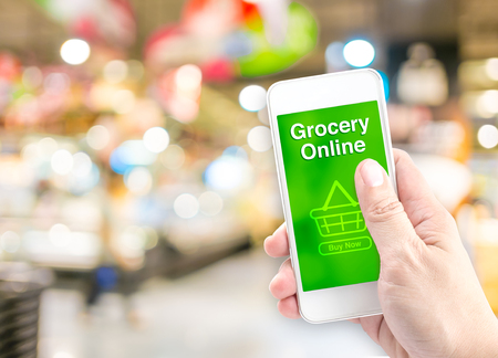 Photo pour Hand holding mobile with grocery online on screen with blur supermarket background, Online delivery concept. - image libre de droit