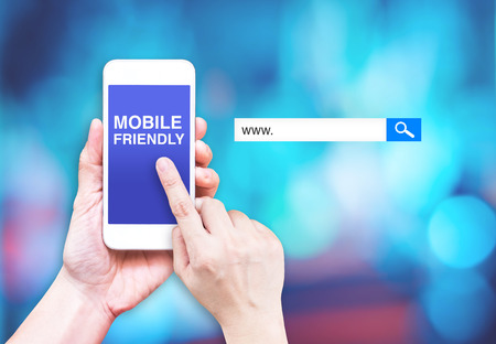 Foto de Hand touch mobile phone with  mobile friendly word with search box at blurred blue background, Digital marketing business concept. - Imagen libre de derechos