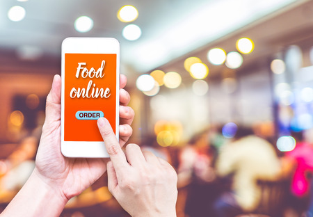 Foto de Hand holding mobile with Order food online with blur restaurant background, food online business concept.Leave space for adding your text. - Imagen libre de derechos
