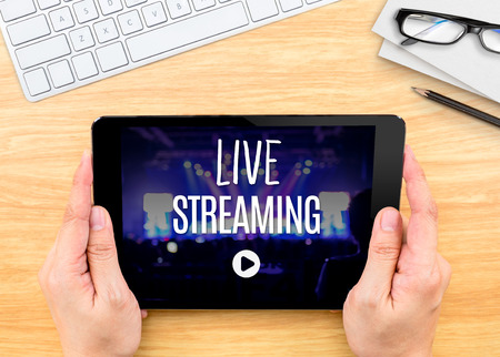 Photo for Hand holding tablet with Live Streaming word on wood table ,Internet marketing concept.. - Royalty Free Image