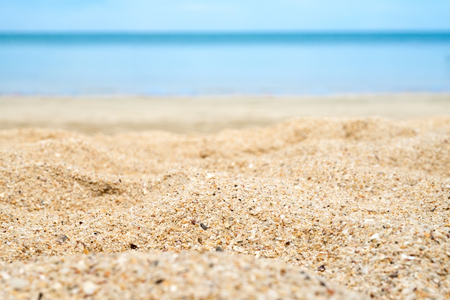 Foto de Close up beach sand with blur sea at background. - Imagen libre de derechos
