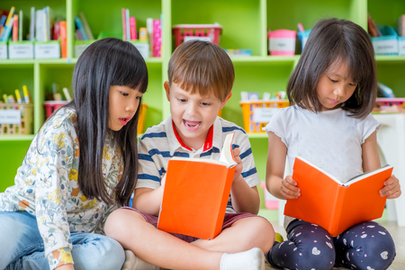 Photo pour Children sitting on floor and reading tale book  in preschool library,Kindergarten school education concept - image libre de droit