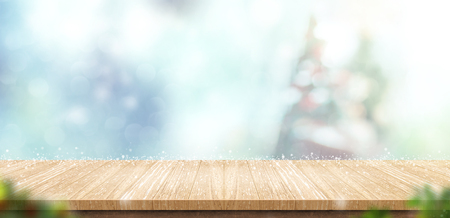Foto de Empty wooden table with abstract blur christmas tree and snow falling background with bokeh,Holiday backdrop,Mock up banner for display of product for promotion online. - Imagen libre de derechos