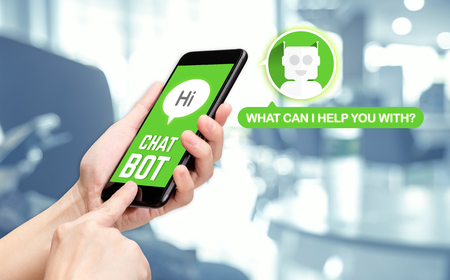 Foto de Hand holding mobile chat with bot on mobile message app with blur office background,artificial intelligence(ai) bot. - Imagen libre de derechos