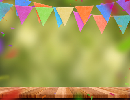Photo pour Colorful flag banner and confetti on wood table with blur green tree bokeh background, Template mock up for montage of product.party garland holiday backdrop for display design - image libre de droit