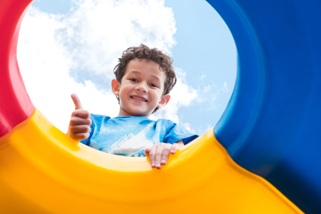 Foto de kid boy thumbs up and having fun to play on children's climbing toy at school playground,back to school activity,looking up view. - Imagen libre de derechos