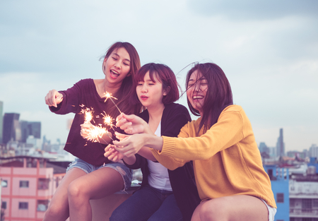 Foto de Happy group of asia girl friends enjoy and play sparkler at roof top party at evening sunset,Holiday celebration festive,teeage lifestyle,freedom and fun - Imagen libre de derechos