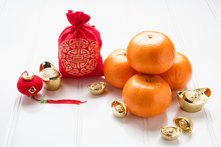 Photo pour Chinese New year,ang pow red felt fabric bag with gold ingots and tangerine oranges on white wood table top,Chinese Language mean Happiness and on ingot mean wealthy - image libre de droit