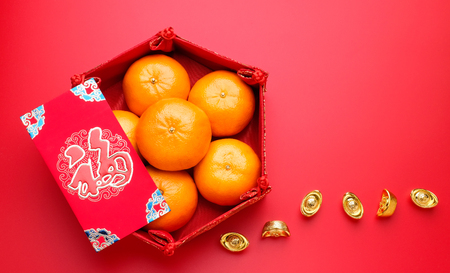 Photo pour Group of orange tangerine in Chinese pattern tray and envelope packet ang pow with gold ingots on red table top. Chinese new year concep.Chinese Language on envelop is happiness,on ingot is wealthy - image libre de droit