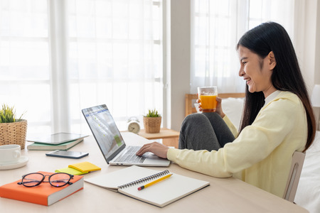 Photo for Asian female sit with knees up use social media with laptop on table and drink orange juice in bedroom at home.Work at home concept.work from home.relax lifestyle - Royalty Free Image