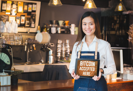 Photo for Close up woman barista holding tablet and show bitcoin accepted here on tablet screen at cafe counter bar,seller coffee shop accept payment by crypto currency.digital money concept.modern waitress - Royalty Free Image
