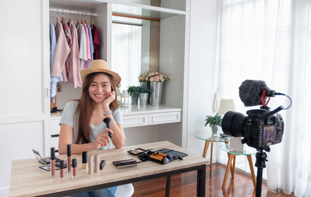 Photo pour Asian young female blogger recording vlog video with makeup cosmetic at home online influencer on social media concept.live streaming viral - image libre de droit