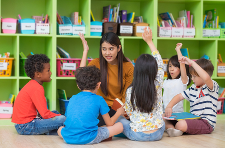 Photo pour Asian female teacher teaching and asking mixed race kids hand up to answer in classroom,Kindergarten pre school concept - image libre de droit