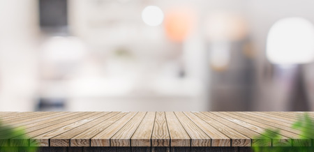 Photo pour Empty brown wooden plank table top with blurred home kitchen with blur foreground leaf,Mock up template for display or montage of your design,Banner for advertise of product,panorama view - image libre de droit