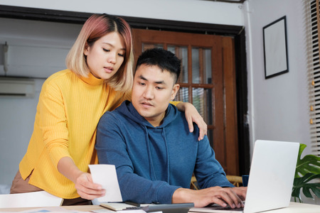 Photo pour Asian couple together calculate home budget with paper bill and laptop in new house at table in kitchen - image libre de droit