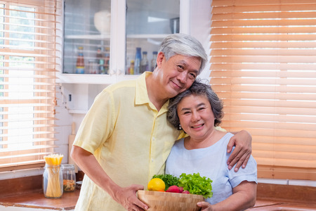 Foto de Portrait happiness asian senior couple  at kitchen with a bowl of fresh salad and looking at camera,aging at home conept. - Imagen libre de derechos