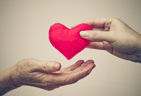 Photo for take care of old mother - young female hand giving a red heart to old hand of a mother - Royalty Free Image