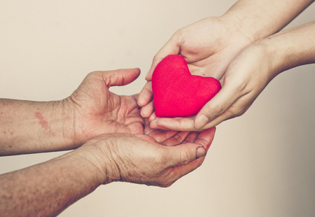 Foto per take care of old mother - young female hand giving a red heart to old hand of a mother - Immagine Royalty Free