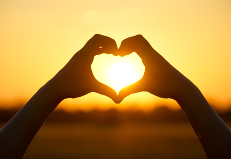 Photo for hands forming a heart shape with sunset silhouette - Royalty Free Image