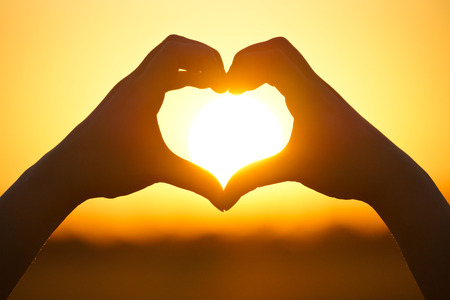 Photo pour hands forming a heart shape with sunset silhouette - image libre de droit