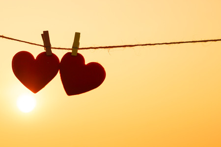 Photo pour red hearts hung on the rope with sunset silhouette - image libre de droit