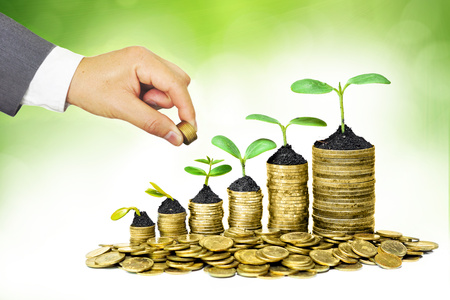 Foto de Hands of businessman giving coins to trees growing on coins in germination sequence  Business with csr practice - Imagen libre de derechos