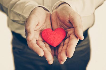 Foto de Businessman giving a red heart to a customer on isolated background - Imagen libre de derechos