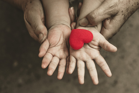 Photo pour old hands holding young hand of a baby with red heart - image libre de droit
