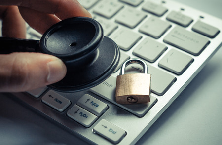 Foto de hand holding a stethoscope over computer keyboard with a security lock - computer system check and maintenance concept - Imagen libre de derechos