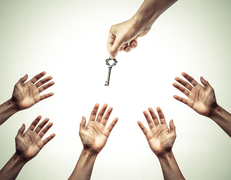 Photo pour hand giving a key to many hands - giving help, opportunity, success concept - image libre de droit