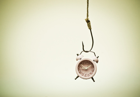 Photo for A clock hung on a fish hook - Time trap concept - Royalty Free Image