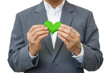 Foto de Businessman holding a green heart / Business with corporate social responsibility and environmental concern - Imagen libre de derechos