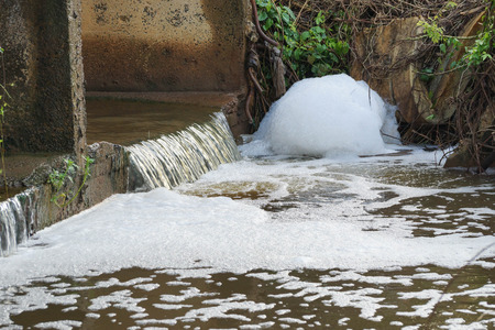 Foto de Water pollution - Waste water full of bubbles released from the industrial ares affecting natural water resources - Imagen libre de derechos