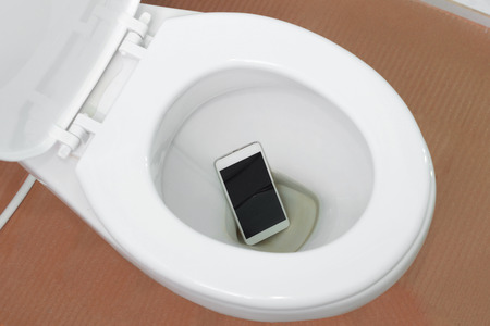 Photo for A white smartphone dropped into a toilet bowl - Royalty Free Image