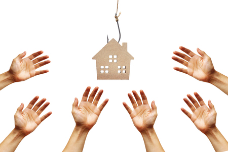Photo pour Hands reaching out for a house on a fish hook / Risks and negative sides of buying a house concept - image libre de droit