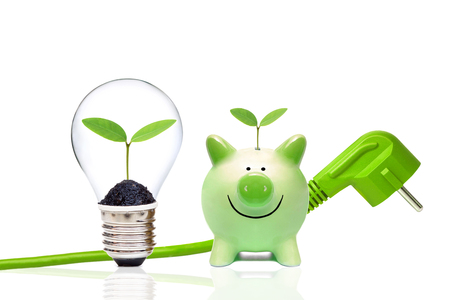 Foto de A green plug with green piggy bank and a light bulb with small green plants / Green energy and saving environment concept - Imagen libre de derechos