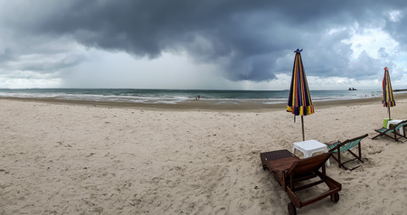 A panorama shot of a beach with imcoming rain storm / Vacation with bad weather concept