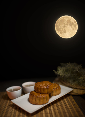 Photo pour Chinese Mid Autumn Festival mooncake and tea on Wooden Bamboo Mat with Dark Background - image libre de droit
