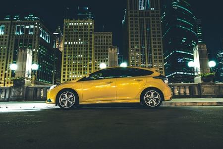 Foto de Downtown Parked Car at Night  Downtown Chicago Parking Space  Five Doors Yellow Car with Lights On  - Imagen libre de derechos