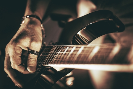 Photo for Guitarist Plays. Electric Guitar Playing Closeup Photo. Rockman Guitar Player Music Theme. - Royalty Free Image