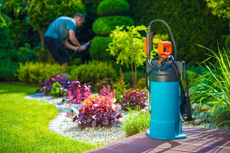 Foto de Garden Pest Control Spray and Male Gardener in the Background. Spraying Pesticides in a Garden. Gardening Theme. - Imagen libre de derechos