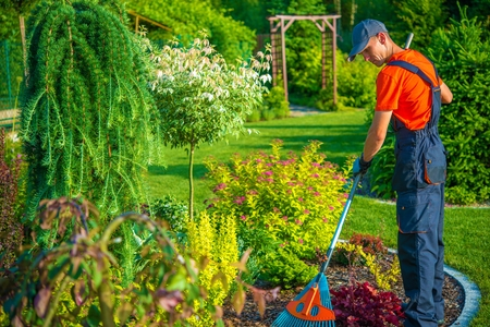 Photo pour Gardener with Rake at Work - image libre de droit