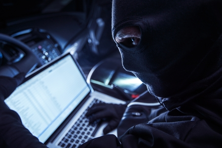 Photo pour Hacker Inside the Car. Car Robber Hacking Vehicle From Inside Using His Laptop. Hacking On board Vehicle Computer. - image libre de droit