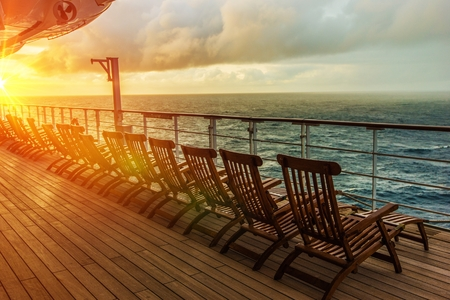 Cruise Ship Wooden Deck Chairs. Cruise Ship Main Deck at Sunset.