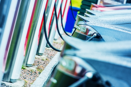 Photo pour Charging Electric Vehicles Using Public Outdoor Electric Chargers. Modern Electric Cars in Use. Future of Transportation. - image libre de droit