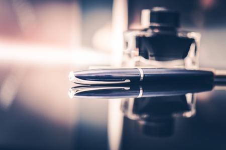 Foto de Corporate Executive Desk. Elegant Stylish Glassy Desk with Fountain Pen For Documents, Contracts and Checks Signing - Imagen libre de derechos