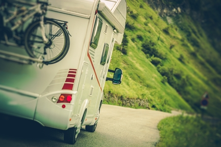 Photo pour Camper Van on the Road. Class C Motorhome Coach with Bikes on the Rear Side Bike Rack. Family RV Travel. - image libre de droit