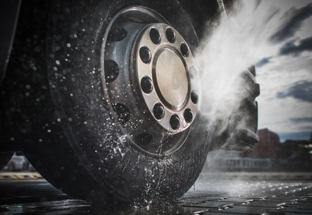 Photo pour Semi Truck Wheels High Pressured Water Washing Closeup Photo. - image libre de droit