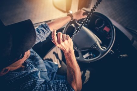 Photo pour Semi Truck Driver Making Conversation with Other Truck Drivers Through CB Radio. - image libre de droit